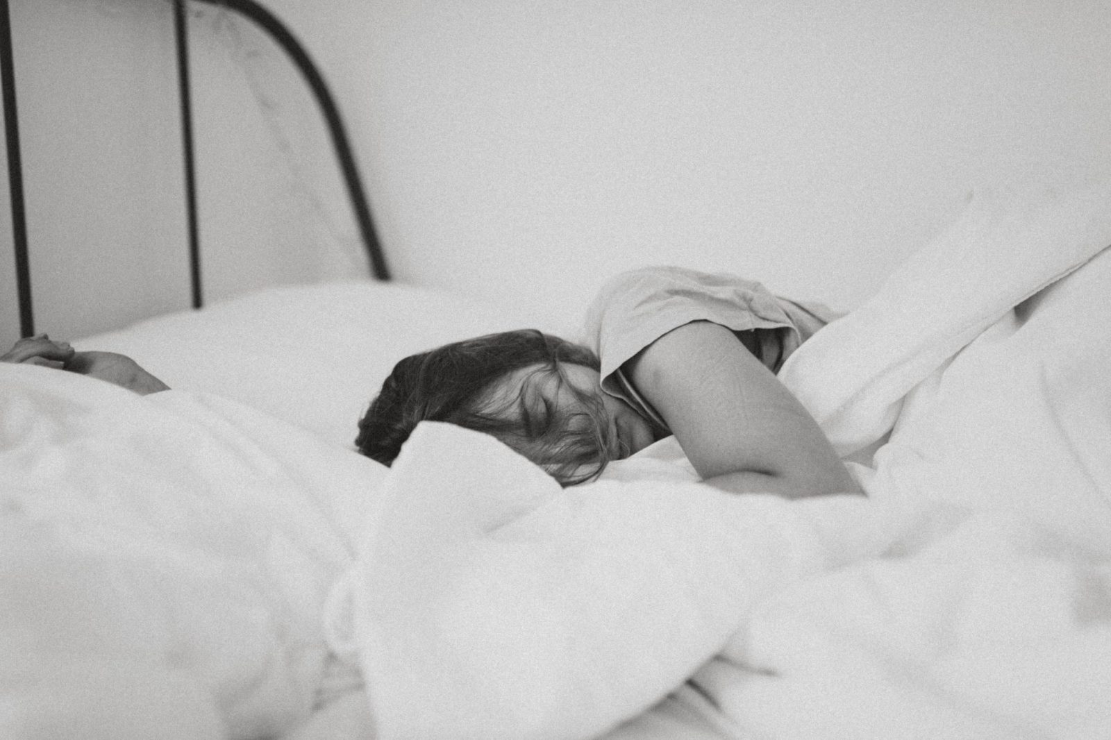 Woman with messy hair is sleeping in a white bed with messy sheets. Showing how to get better sleep.